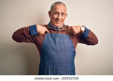 Senior handsome baker man wearing apron standing over isolated white background looking confident with smile on face, pointing oneself with fingers proud and happy.