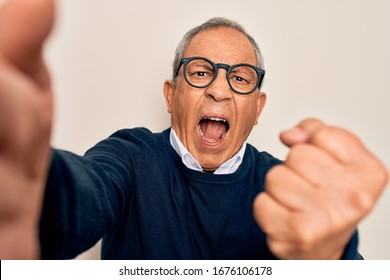 Senior handsome grey-haired man wearing sweater and glasses making selfie by camera annoyed and frustrated shouting with anger, crazy and yelling with raised hand, anger concept