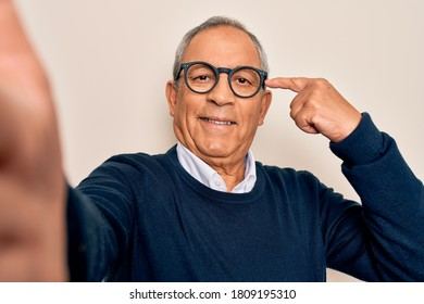 Senior handsome grey-haired man wearing sweater and glasses making selfie by camera very happy pointing with hand and finger