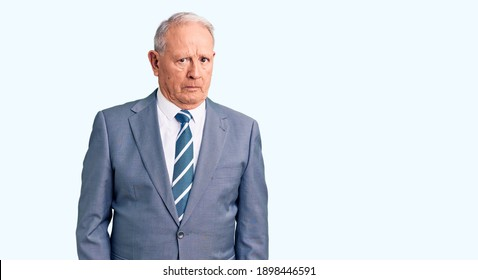 Senior handsome grey-haired man wearing elegant suit skeptic and nervous, frowning upset because of problem. negative person.