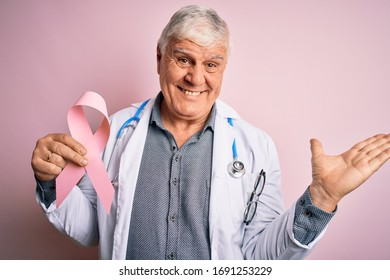 Senior handsome hoary doctor man wearing stethoscope holding pink cancer ribbon very happy and excited, winner expression celebrating victory screaming with big smile and raised hands