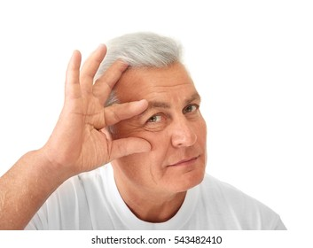 Senior handsome man examining his face on white background