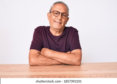 Senior handsome man with gray hair wearing casual clothes and glasses happy face smiling with crossed arms looking at the camera. positive person.
