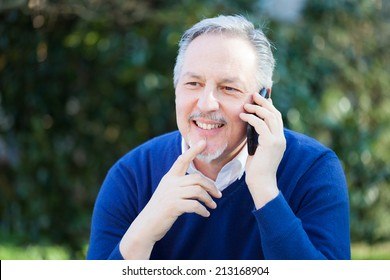 Senior handsome man talking on the phone in a park