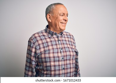 Senior handsome man  wearing casual shirt standing over isolated white background looking away to side with smile on face, natural expression. Laughing confident.