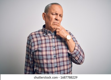 Senior handsome man  wearing casual shirt standing over isolated white background with hand on chin thinking about question, pensive expression. Smiling with thoughtful face. Doubt concept.