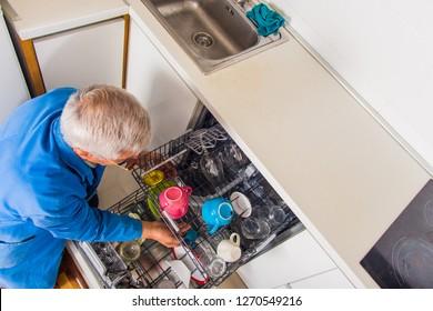 Senior handyman opening dish washer machine in his house