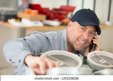 senior handyman taking smartphone call while working on appliance