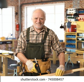 Senior happy casual caucasian handyman working at DIY workshop with tools, belt, wearing gloves. Smiling, looking at camera.