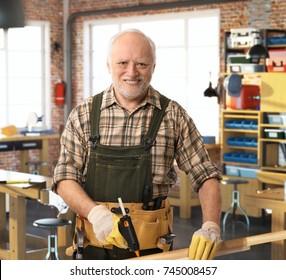 Hochwertiger glücklicher Kaukasier Handwerker, der in der DIY-Werkstatt mit Werkzeugen, Gürteln und Handschuhen arbeitet. Lächeln, Kamera ansehen.