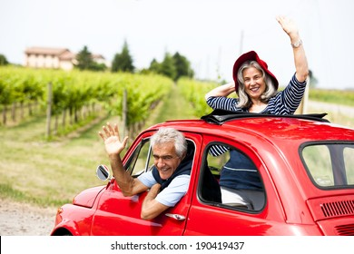 Senior happy couple driving vintage car