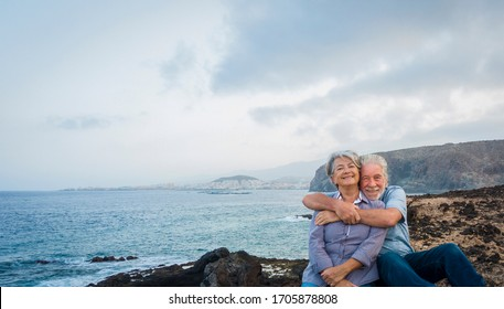 Senior happy couple enjoying a sea excursion  looking at camera. Two elderly people with gray hair, casual clothing. Active retirement concept