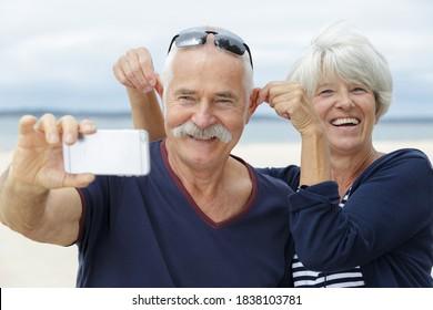 glückliches Ehepaar, das Spaß beim Selbstnehmen hat