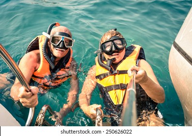 Senior happy couple using selfie stick in tropical sea excursion - Boat trip snorkeling in exotic scenarios - Concept of active elderly and fun around the world - Soft vintage filtered look