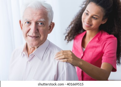 Senior happy elegant man and young pretty caregiver holding hand on man's arm