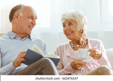 Senior happy smiling couple spending time together reading and drinking tea