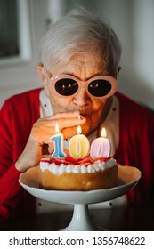 Senior happy well dressed gray haired woman is celebrating her 100th birthday at home.