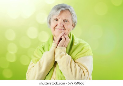 Senior happy woman on green background.
