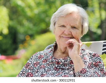 Senior happy woman smiling in garden. MANY OTHER PHOTOS FROM THIS SERIES IN MY PORTFOLIO.