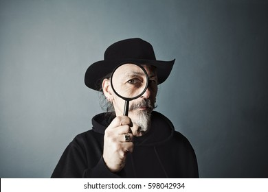 senior in a hat looks at us through a magnifying glass on gray wall background.