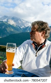 Senior Having A Drink In An Alpine Restaurant