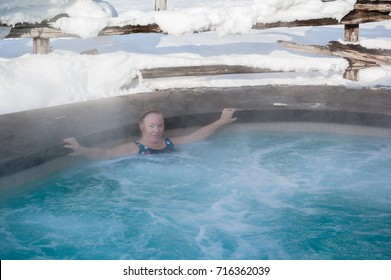 Senior healthy woman relaxing in hot water swimming pool.  Outdoor spa. Healthy treatment. Winter.