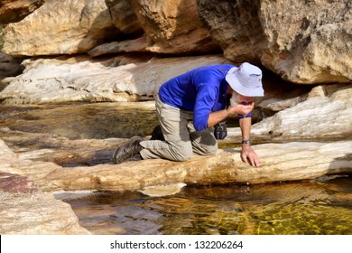 Senior hiker drinks water from mountain river. Shot in Gifberg Mountains, near Wanrhynsdorp, Western Cape, South Africa.