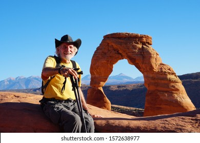 A senior hiker enjoying the views from the Delicate Arch area of Arches National Park.