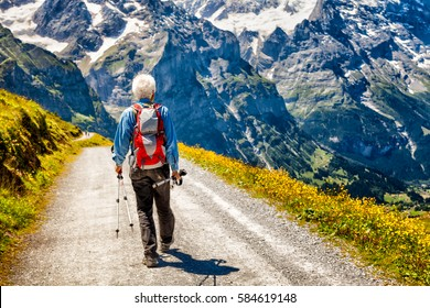 Senior hiker on a trail in the Swiss Alps facing a spectacular view of steep jagged mountains with patches of snow. Yellow wild flowers by gravel path. Concept: Senior adventure travel, independence