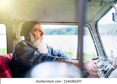 Senior hipster driving a van by countryside, he is tattooed and he wears a white beard