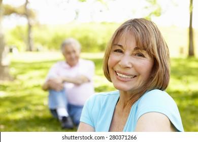 Senior Hispanic Couple Relaxing In Park