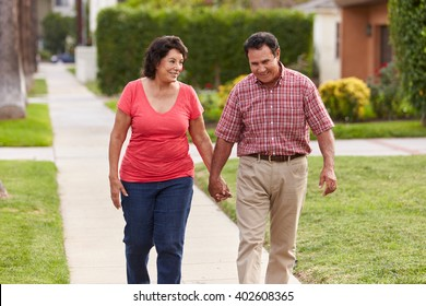 Senior Hispanic Couple Walking Along Sidewalk Together