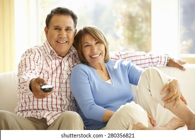 Senior Hispanic Couple Watching TV At Home