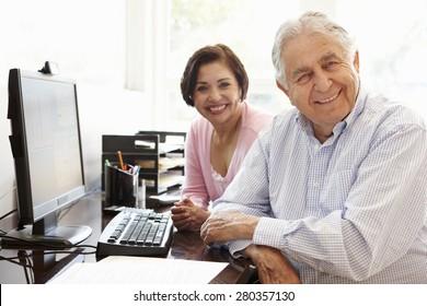 Senior Hispanic couple working on computer at home
