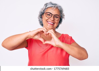 Senior hispanic grey- haired woman wearing casual clothes and glasses smiling in love doing heart symbol shape with hands. romantic concept.