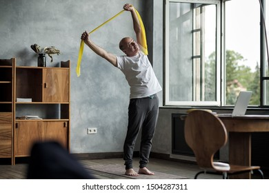 Senior hispanic man doing side bend exercise using resistance band practicing alone in the living room.