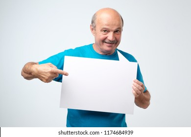 Senior hispanic man with mustache holds the white sign in a studio white background. look here, great offer