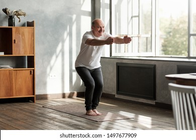 Senior hispanic man practicing yoga indoors at living room doing Chair pose or Utkatasana