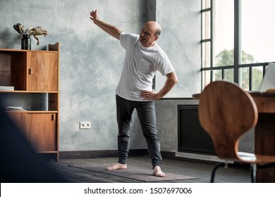 Senior hispanic man practicing yoga trikonasana pose at the living room