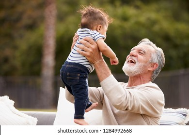 Senior Hispanic man sitting in the garden lifting his baby grandson in the air and smiling to him