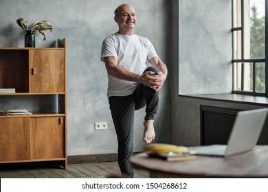Senior hispanic man standing in one leg yoga balance. Healthy lifestyle at old age