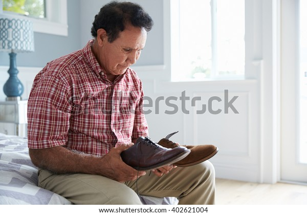 Senior Hispanic Man Suffering With Dementia Trying To Dress
