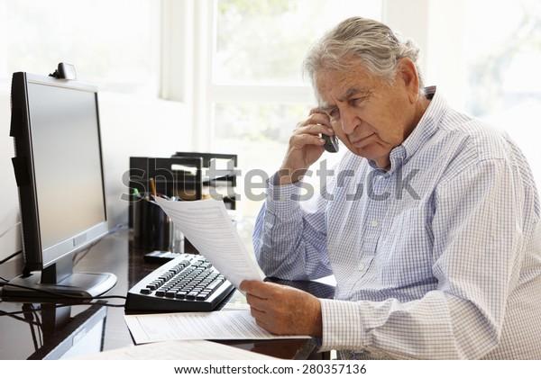 Senior Hispanic man working on computer at home