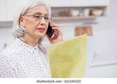 Senior housewife talking on mobile phone in kitchen