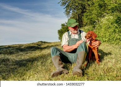 Senior hunter with dungarees and rubber boots sits on the mowed pasture in the evening sun and lovingly holds his little Irish Setter puppy in his arms.