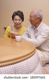 senior husband and wife looking at mobile in kotatsu