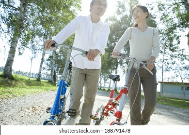 senior husband and wife pushing their bicycle