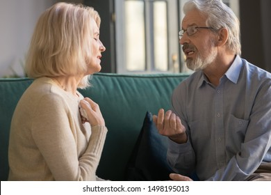 Senior husband and wife sit on couch at home talk dispute on family relations problem, stubborn mature couple having disagreement misunderstanding speak discuss health troubles or relationships