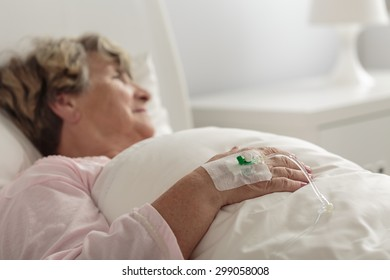 Senior ill woman connected to drip in hospital