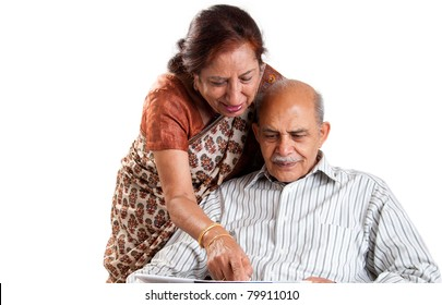 A senior Indian / Asian couple pointing at a newspaper - isolated on white